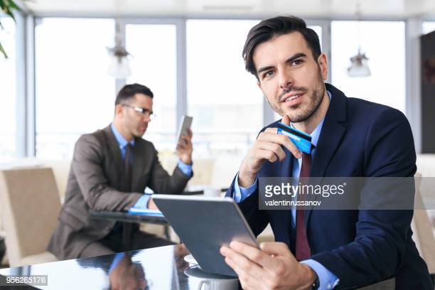 Businessman using credit card and tablet in cafe