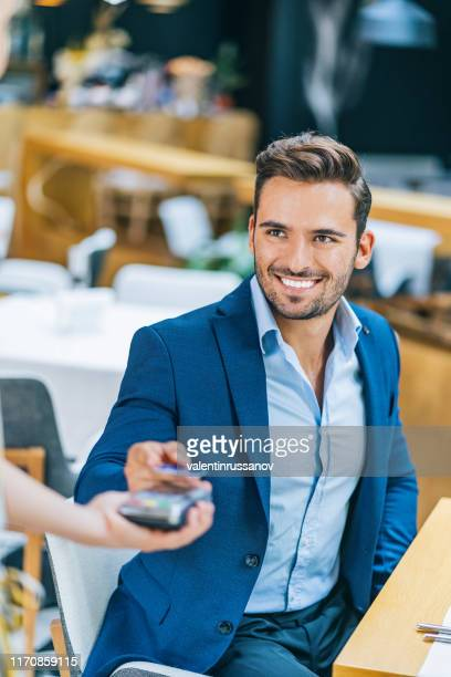 businessman using credit card for contactless payment in restaurant - mid adult men stock pictures, royalty-free photos & images