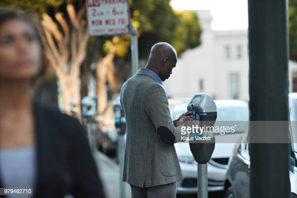 businessman using credit card to pay for parking - parking meter stock photos and pictures