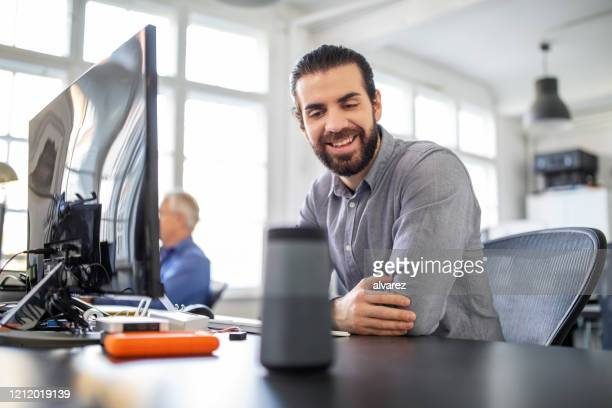 businessman using digital speaker at office - assistant stock pictures, royalty-free photos & images