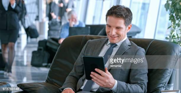 Businessman using digital tablet at airport
