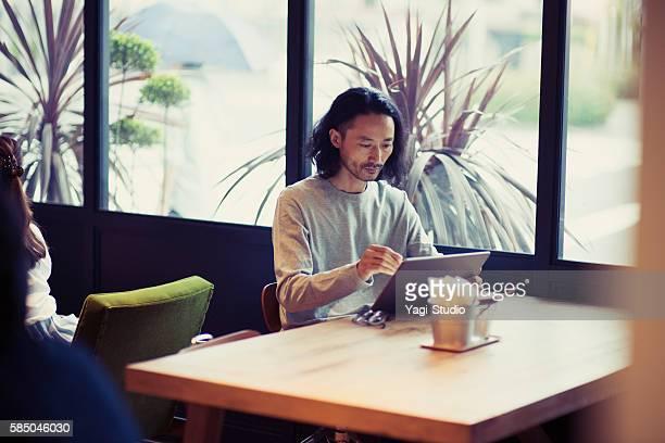 businessman using digital tablet at cafe - カフェ ストックフォトと画像