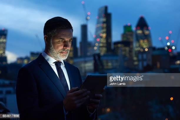 Businessman using digital tablet at night