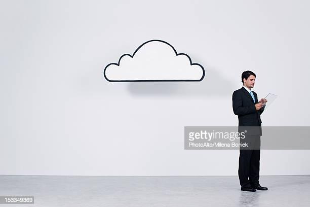 Businessman using digital tablet beneath cloud representing cloud computing