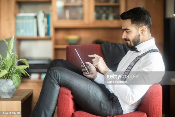 businessman using digital tablet in armchair - sigrid gombert stock pictures, royalty-free photos & images