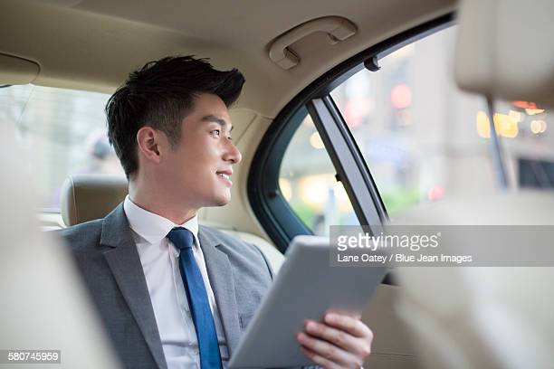 Businessman using digital tablet in car back seat