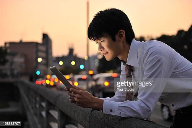 Businessman using digital tablet in city