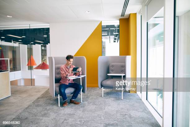 businessman using digital tablet in creative office - gray jeans stock pictures, royalty-free photos & images