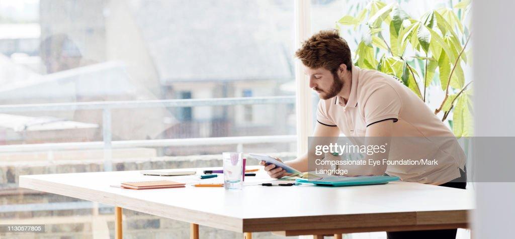 Businessman using digital tablet in modern office : Stock Photo
