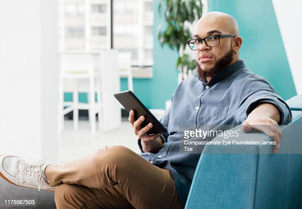 """businessman using digital tablet in modern open plan office - """"compassionate eye"""" stock pictures, royalty-free photos & images"""