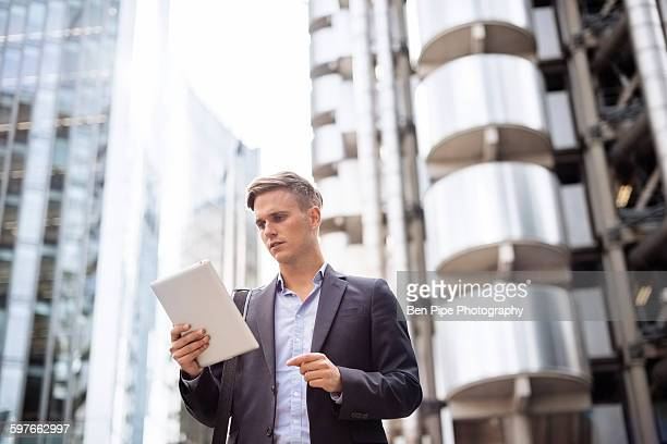 Businessman using digital tablet in street, London, UK