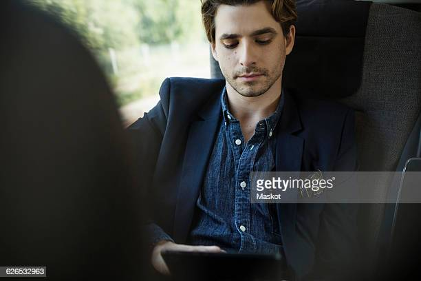 Businessman using digital tablet in train