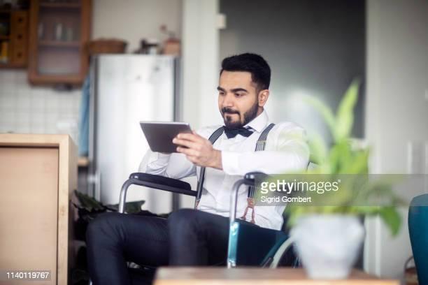 businessman using digital tablet in wheelchair - sigrid gombert stock-fotos und bilder