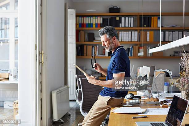 Businessman using digital tablet leaning on desk