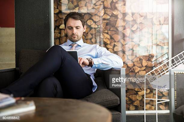 Businessman using digital tablet on chair