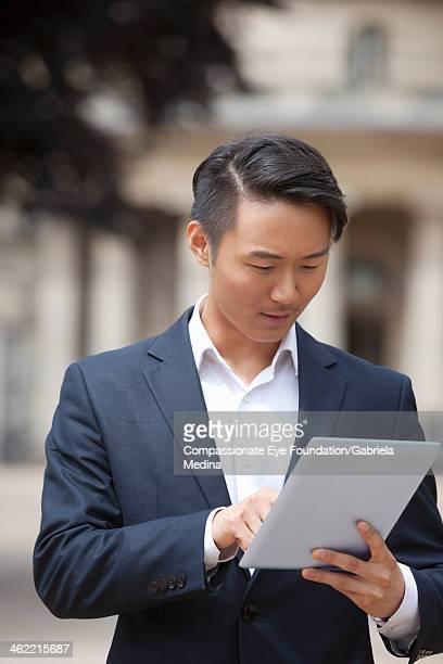 Businessman using digital tablet on city street