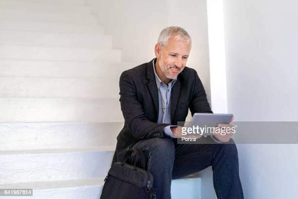 Businessman using digital tablet on steps
