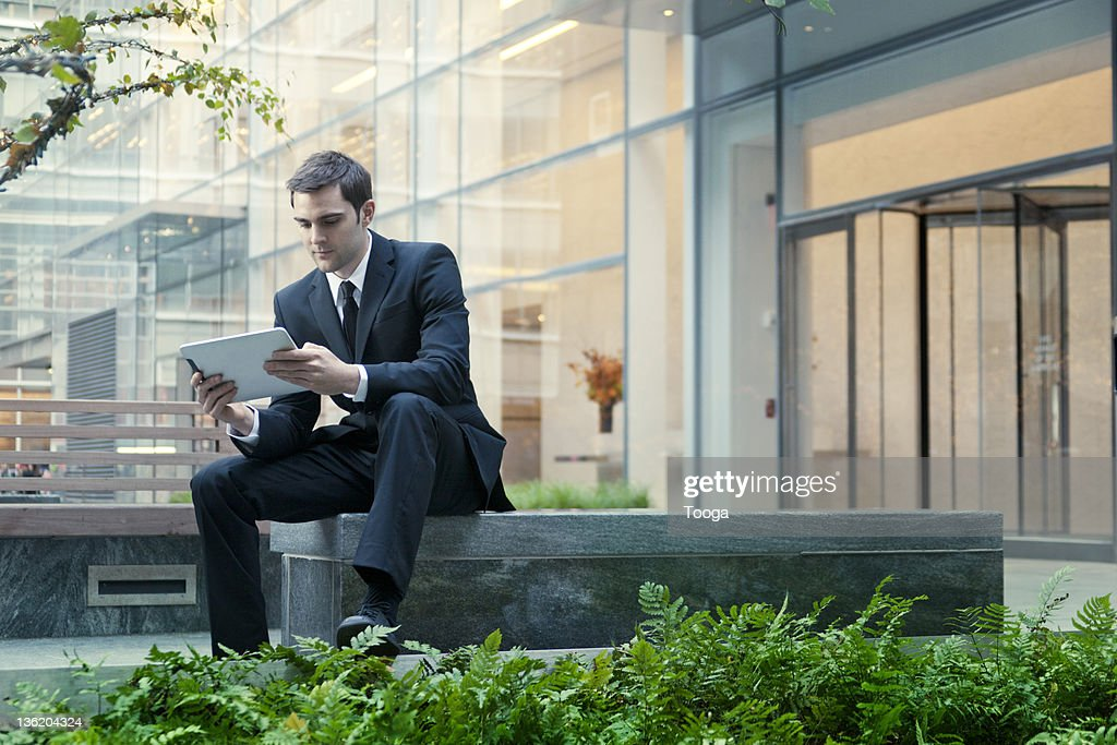Businessman using digital tablet outdoors : ストックフォト