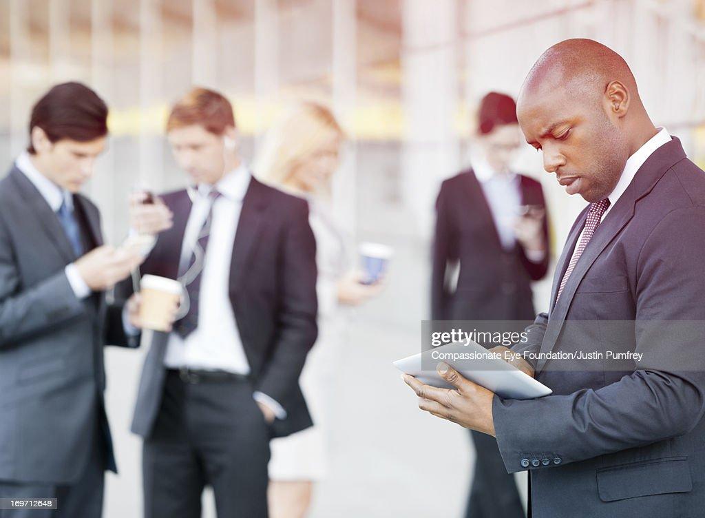 Businessman using digital tablet outdoors : Stock Photo