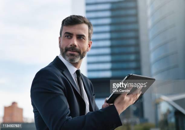businessman using digital tablet - cris cantón photography fotografías e imágenes de stock