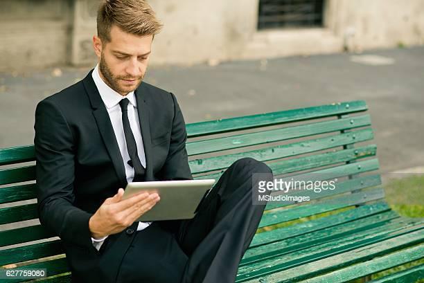 実業家デジタルタブレットを使用しています。 - 男性用ベスト ストックフォトと画像