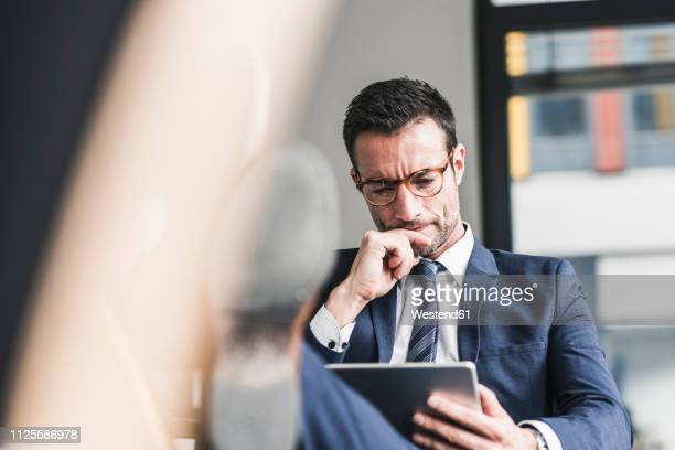 businessman using digital tablet, sitting in office with feet up - formal businesswear stock pictures, royalty-free photos & images