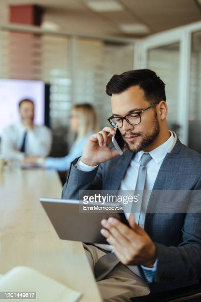 businessman using digital tablet while talking on mobile phone - incidental people stock pictures, royalty-free photos & images