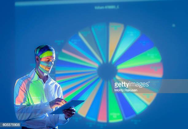 Businessman using digital tablet with projected financial data