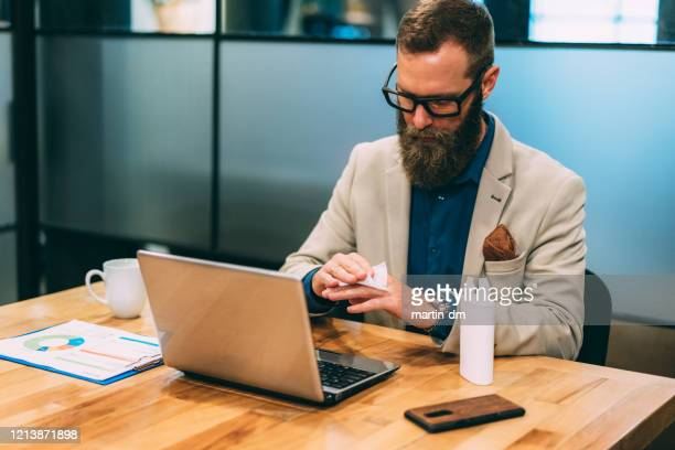 businessman using disinfection wipes during covid-19 - antiseptic wipe stock pictures, royalty-free photos & images