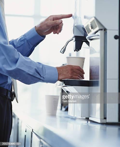 Businessman using drinks machine, close-up
