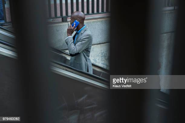 Businessman using escalator from metro station and talking on smartphone
