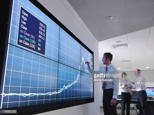 businessman using graphs on screen - actuación conceptos fotografías e imágenes de stock