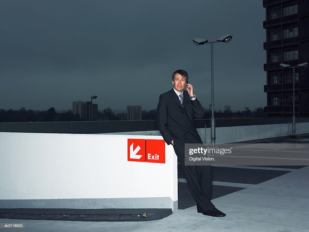 Businessman Using His Mobile Phone in a Car Park at Night : Stock Photo
