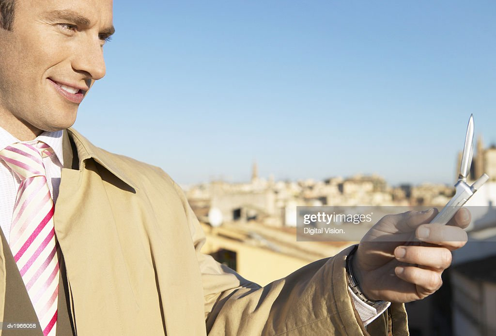 Businessman Using His Mobile Phone in the City : Stock Photo