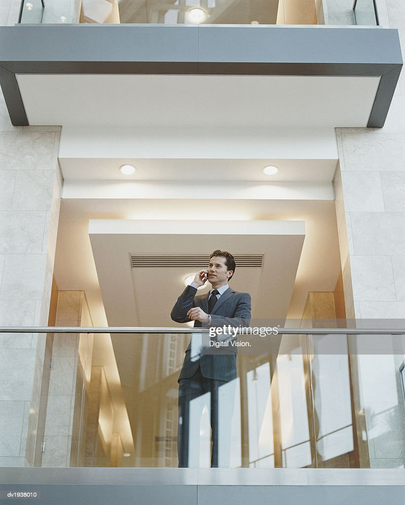 Businessman Using His Mobile Phone Standing on the Balcony of an Office Building : Stock Photo