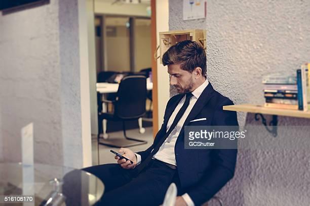 実業家は彼の携帯電話を使用して、開放的なロビー。