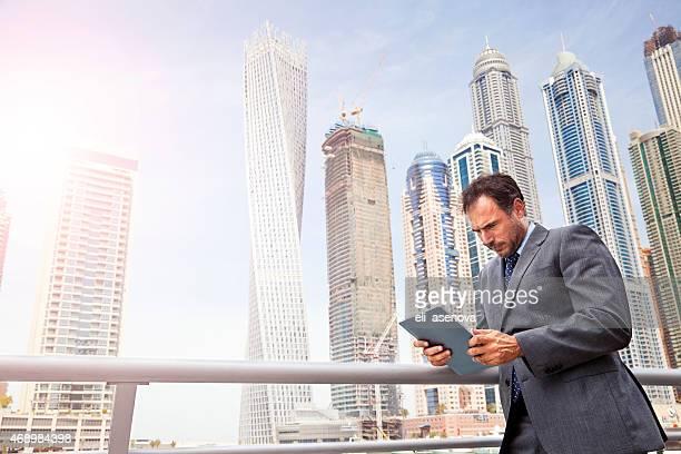 Businessman using his tablet in Dubai Marina.