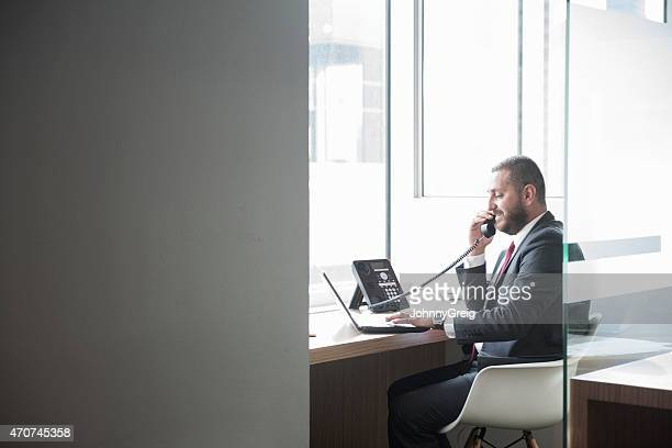businessman using landline phone and laptop at desk - fastnät bildbanksfoton och bilder