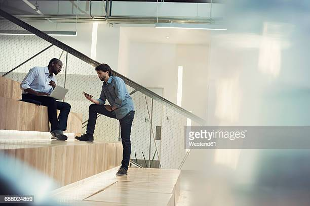 businessman using laptop and discussing with colleague - coordinazione foto e immagini stock