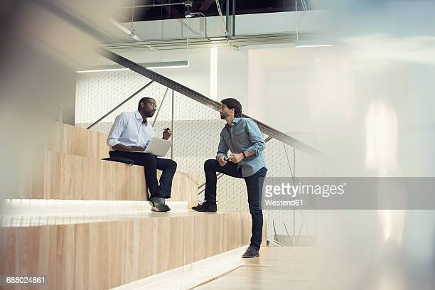 Businessman using laptop and discussing with colleague
