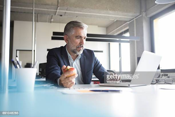 Businessman using laptop and eating an apple at office desk