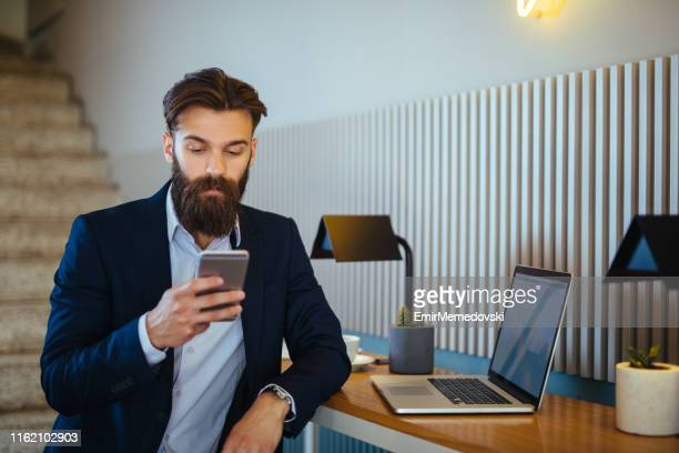 businessman using laptop and smart phone in the office - emir memedovski stock pictures, royalty-free photos & images