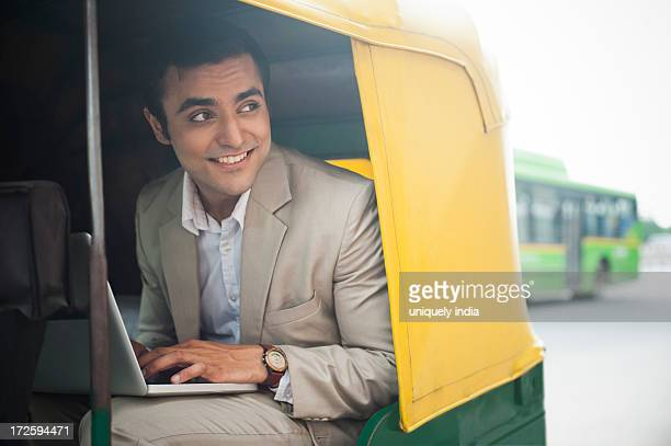 Businessman using laptop and smiling while traveling in an auto rickshaw