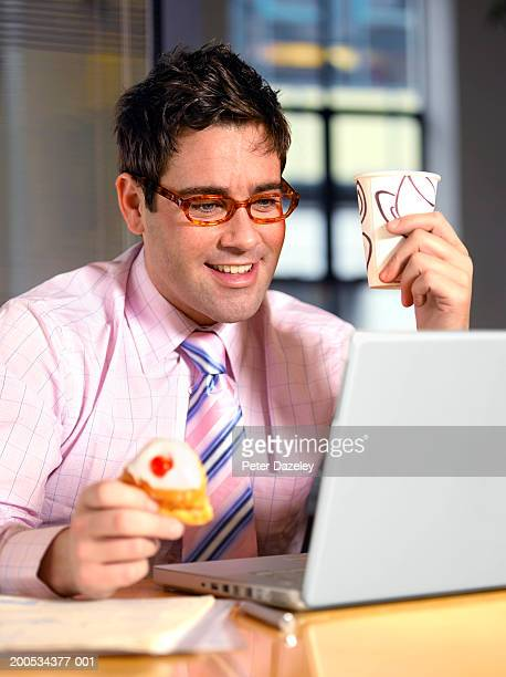 Businessman using laptop at desk, holding cup and cake, smiling