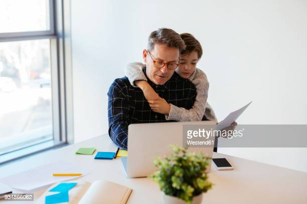 businessman using laptop at desk in office with son embracing him - things that go together stock photos and pictures