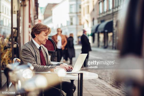businessman using laptop at sidewalk cafe - northern european stock photos and pictures