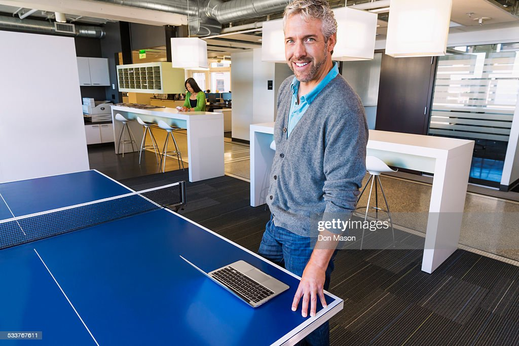 Businessman using laptop at table tennis table in office : Foto stock