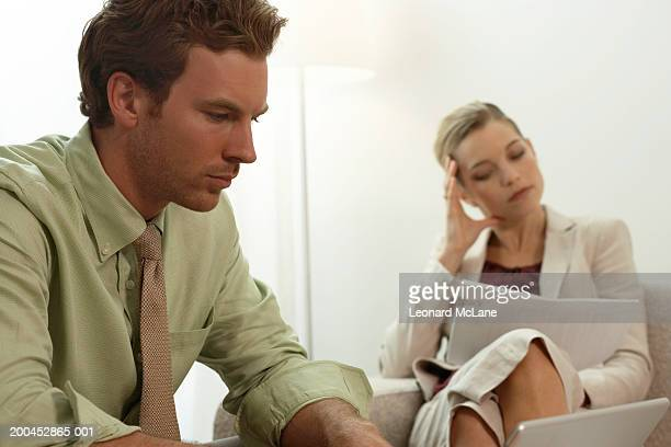Businessman using laptop, businesswoman sitting in background