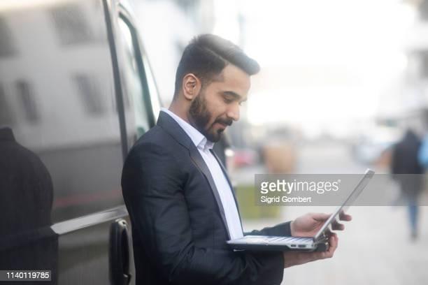 businessman using laptop by car - sigrid gombert stock-fotos und bilder