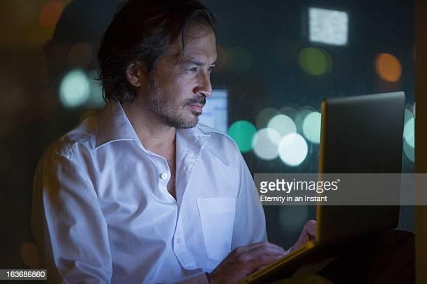Businessman using laptop computer at night